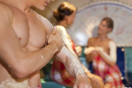 Three friends - two women, one man - doing wellness in the sauna of a thermal bath; close-up of the man in front photo