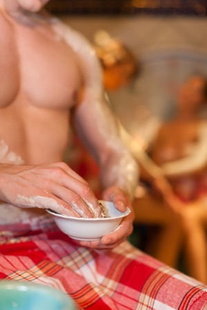 two women and one man: Three friends - two women, one man - doing wellness in the sauna of a thermal bath; close-up of the man in front