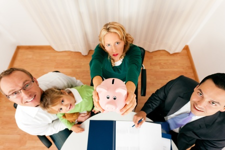 advising: Family with their consultant  assets, money or similar  doing some financial planning - symbolized by a piggy bank they are holding in their hand