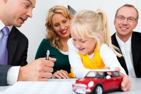 agente comercial: Familia con sus activos de consultores, dinero o similares, haciendo un poco de planificación financiera - simbolizado por un coche de juguete que están sosteniendo en su mano