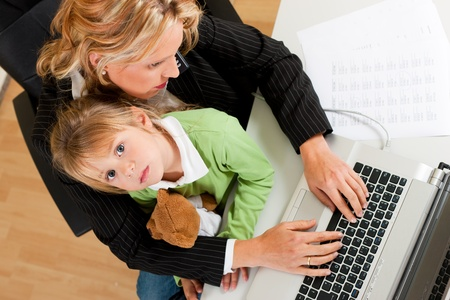 working animal: Family Business - telecommuter Businesswoman and mother is working in the internet while her daughter looks to the viewer   Stock Photo