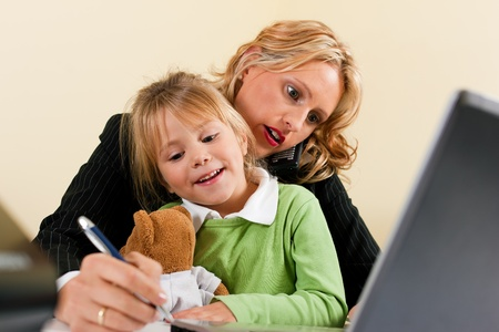 telecommuting: Family Business - telecommuter Businesswoman and mother is working in the internet while her daughter is playing with her teddy