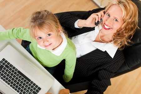 telecommuter: Family Business - telecommuter Businesswoman and mother with kid on her lap is making a phone call, both are looking to the viewer