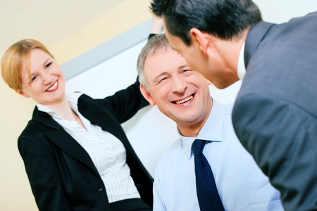 enjoyable: Small business team in the office in front of a whiteboard discussing something rather enjoyable, people are cheerful