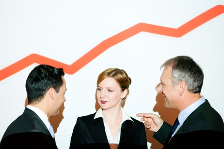 Business team standing in front of business graph projected on wall  video projector used as light source    photo