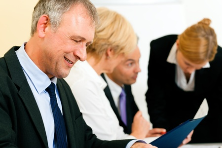 convince: Small business team in the office in front of a whiteboard discussing a project and some documents   Stock Photo