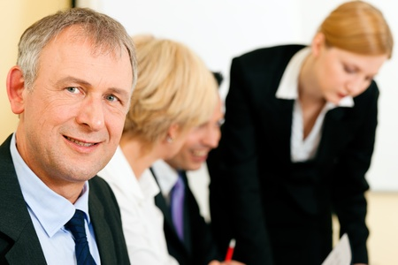 convince: Small business team in the office in front of a whiteboard discussing a project and some documents, one is looking in the camera   Stock Photo
