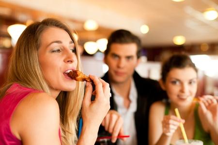 ätande: Tre vänner på en restaurang eller diner äta kycklingvingar, tagna med befintligt ljus, mycket selektiv fokus