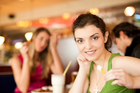 out to lunch: Three friends in a restaurant or diner eating fries and drinking milkshakes, shot with available light, very selective focus Stock Photo