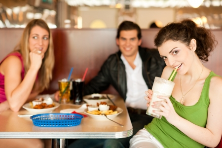 eating out: Three friends in a restaurant or diner eating fries and drinking milkshakes, shot with available light, very selective focus Stock Photo