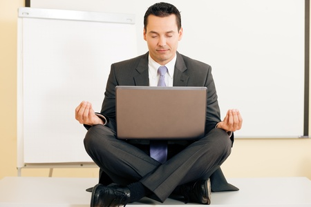 balance life: Man sitting with laptop legs crossed doing yoga