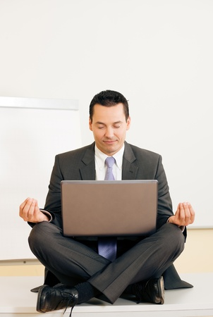 Man sitting with laptop legs crossed doing yoga Stock Photo - 12719344