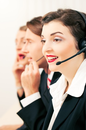 competent: Group of three customer care representatives in a call center with headphones