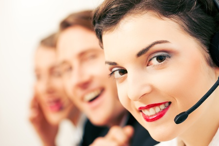 Group of three customer care representatives in a call center with headphones photo