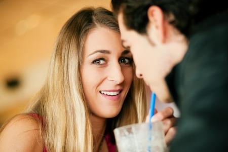 coquetear: Pareja en un restaurante o comedor, bebiendo un batido de leche con una pajita, un disparo con la luz disponible, el enfoque muy selectivo Foto de archivo