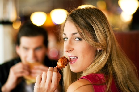 Couple in a restaurant or diner eating a hamburger and chicken wings flirting the while, shot with available light, very selective focus Stock Photo - 12721929