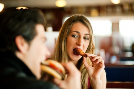 fast eat: Couple in a restaurant or diner eating a hamburger and chicken wings flirting the while, shot with available light, very selective focus Stock Photo