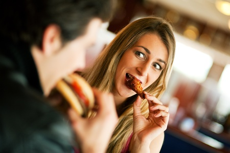 woman eat: Couple in a restaurant or diner eating a hamburger and chicken wings flirting the while, shot with available light, very selective focus Stock Photo