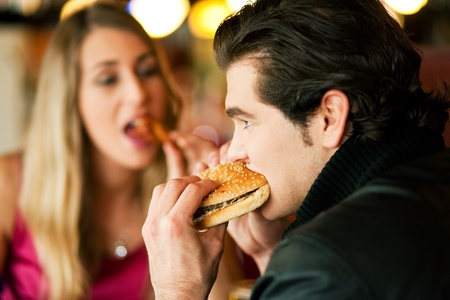chicken burger: Couple in a restaurant or diner eating a hamburger and chicken wings flirting the while, shot with available light, very selective focus Stock Photo