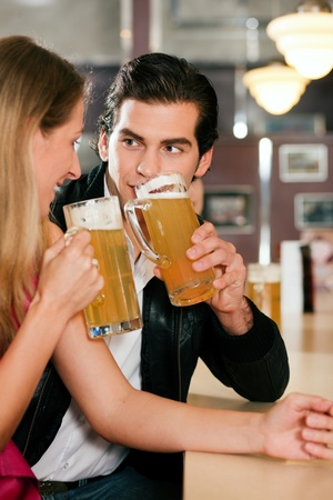Couple in a bar or restaurant drinking beer, flirting very obviously having a lot of fun photo