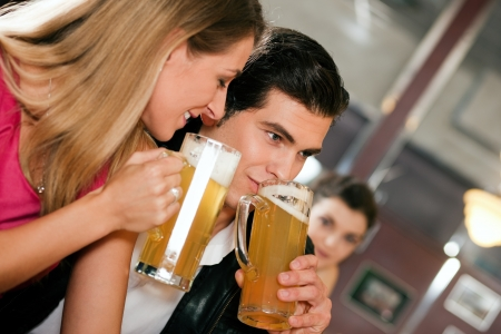 Group of people in a bar or restaurant drinking beer, one couple flirting very obviously having a lot of fun photo