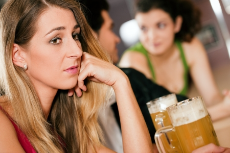 Group of people in a bar or restaurant drinking beer, woman in front being sad since her boyfriend is flirting with another girl dumping her photo
