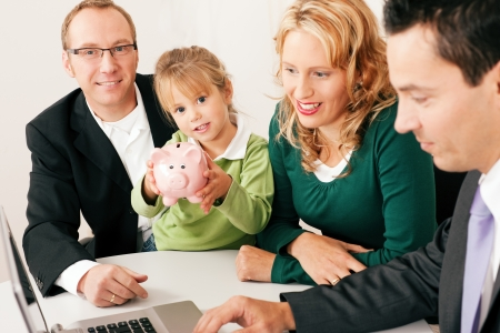 financial adviser: Family with their consultant  assets, money or similar  doing some financial planning - symbolized by a piggy bank in the front  Stock Photo