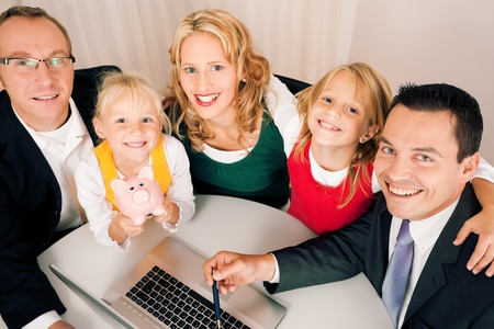 tax consultants: Family with their consultant  assets, money or similar  doing some financial planning - symbolized by a piggy bank in the front  Stock Photo