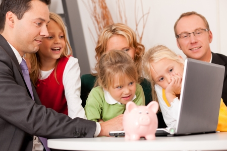 insurance consultant: Family with their consultant  assets, money or similar  doing some financial planning - symbolized by a piggy bank in the front  Stock Photo