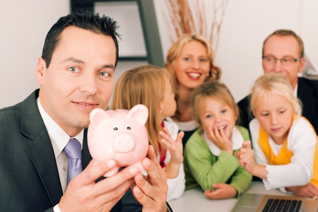 Family with their consultant  assets, money or similar  doing some financial planning - symbolized by a piggy bank in the front, the consultant in front looking at the camera photo
