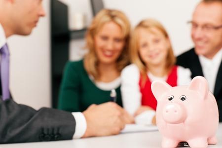 planificaci�n familiar: Familia con sus activos de consultores, dinero o similares, haciendo un poco de planificaci�n financiera - simbolizado por una alcanc�a en el foco delantero s�lo en la hucha