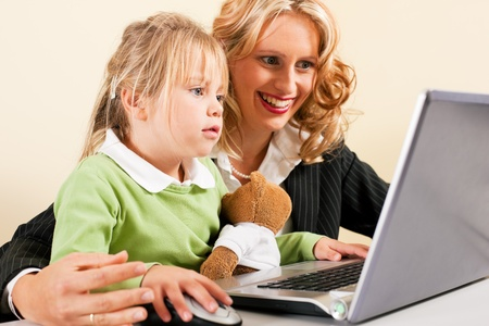 telecommuter: Family Business - telecommuter Businesswoman and mother showing her little daughter how these computer and internet things work