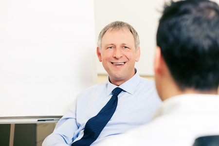 coffee meeting: Two Businesspeople - men - discussing in front of a flipchart  The mood is cheerful  Stock Photo