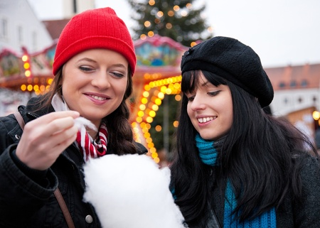 algodon de azucar: Dos mujeres en el mercado de Navidad comiendo algodón de azúcar frente a una cabina, hace frío