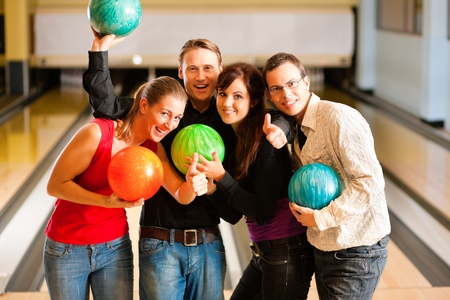 recreation: Group of four friends in a bowling alley having fun, holding their bowling balls
