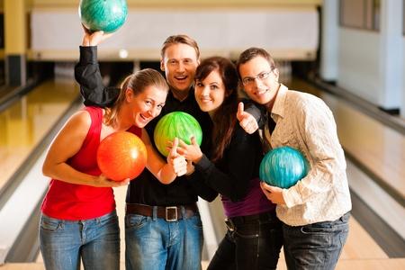 bowling: Grupo de cuatro amigos en un boliche de divertirse, la celebraci�n de sus bolas de bowling Foto de archivo