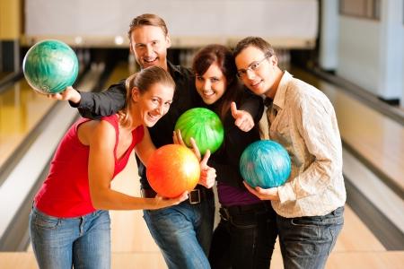 bolos: Grupo de cuatro amigos en un boliche de divertirse, la celebraci�n de sus bolas de bowling Foto de archivo