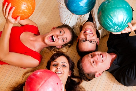 bowling alley: Group of four friends lying in a bowling alley having fun, holding their bowling balls above them