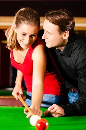 Couple homme et la femme dans une salle de billard jouer au snooker