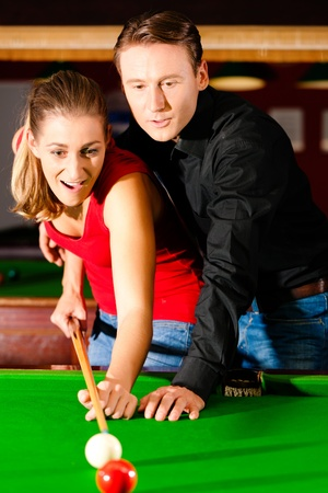 Couple  man and woman  in a billiard hall playing snooker photo