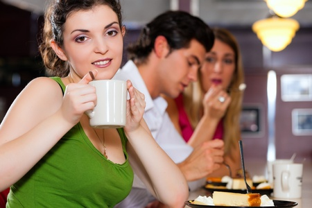Three friends in a restaurant or diner eating cheesecake and drinking coffee photo