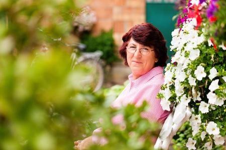 massif de fleurs: Femme de d�tente dans son jardin pr�s de son parterre de fleurs