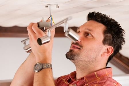 Worker is installing a luster in a house on the ceiling photo