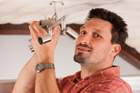 luster: Worker is installing a luster in a house on the ceiling Stock Photo