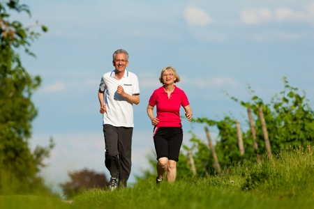 Mature or senior couple doing sport outdoors, jogging down a path in summer photo