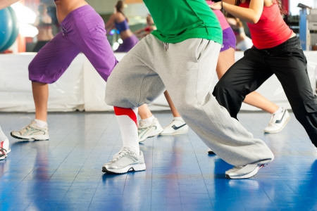 cardio fitness:  Young people  only legs to be seen  doing Zumba training or dance workout in a gym