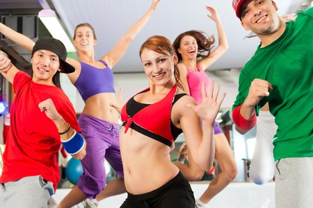 Fitness - Young people doing Zumba training or dance workout in a gym Stock Photo - 12904844