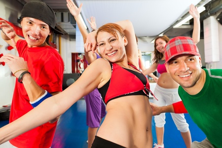 Fitness - Young people doing Zumba training or dance workout in a gym photo