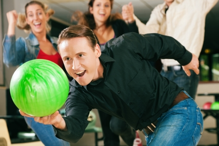 bowling: Group of four friends in a bowling alley having fun, three of them cheering the one in charge to throw the ball