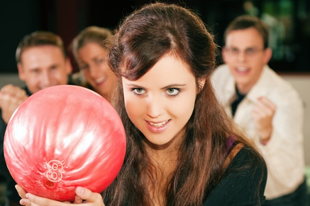 spiel: Group of four friends in a bowling alley having fun, three of them cheering the one in charge to throw the ball
